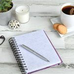 high-angle-view-of-a-blank-notepad-journal-diary-on-a-light-wooden-desk-or-table-overhead-flat-lay_t20_B8lKGv